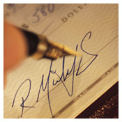 A close up of a pen signing a check